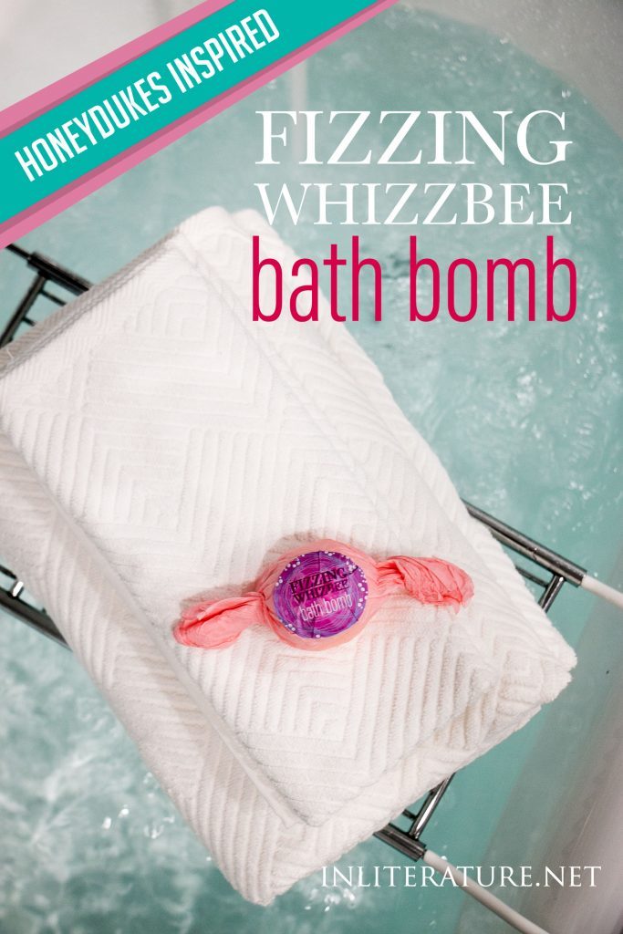 Honeydukes inspired fizzing whizzbee homemade bath bombs on white fluffy towels over a modern bathtub